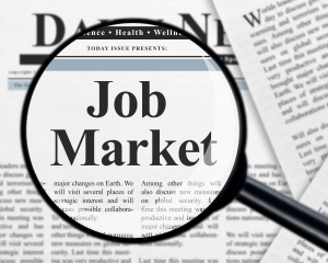 Job market headline under magnifying glass